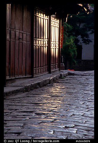 Cobblestone street and wooden doors at sunrise. Lijiang, Yunnan, China