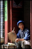 Naxi woman at doorway selling broiled corn. Lijiang, Yunnan, China