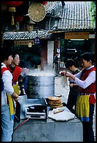 Naxi women selling dumplings and Naxi baba flatbread. Lijiang, Yunnan, China (color)
