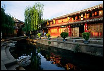 Buildings on Square street reflected in canal, sunrise. Lijiang, Yunnan, China