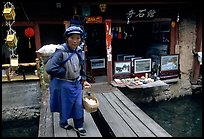 Naxi woman peddling eggs  to local residents walks acros a canal. Lijiang, Yunnan, China