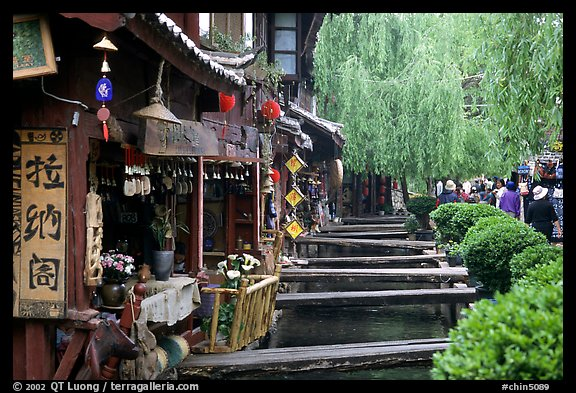 Bridges leading to restaurants and residences across the canal. Lijiang, Yunnan, China