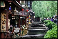 Bridges leading to restaurants and residences across the canal. Lijiang, Yunnan, China (color)
