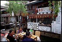 Women eat outside the Snack Food in Lijiang restaurant. Lijiang, Yunnan, China (color)