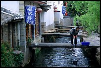 Woman fills up a water buck in the canal. Lijiang, Yunnan, China (color)