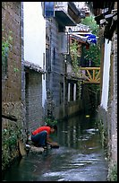 Woman washes clothes in the canal. Lijiang, Yunnan, China