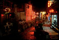 Red lanterns reflected in a canal at night. Lijiang, Yunnan, China (color)