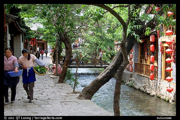 Naxi women walk along a canal. Lijiang, Yunnan, China