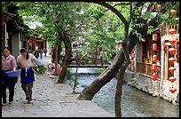 Naxi women walk along a canal. Lijiang, Yunnan, China (color)