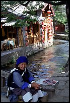 Elderly naxi woman peddles candies near a canal. Lijiang, Yunnan, China (color)