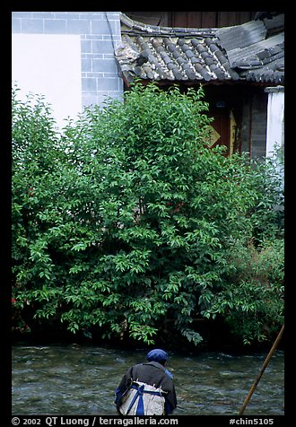 Naxi woman sitting next to a canal. Lijiang, Yunnan, China