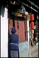 Naxi woman at the door of her wooden house. Lijiang, Yunnan, China (color)