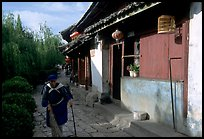 Naxi woman sweeps the floor at the door of her wooden house. Lijiang, Yunnan, China ( color)
