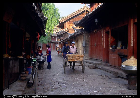 Early morning activity in a cobblestone street. Lijiang, Yunnan, China (color)