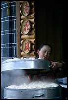 Woman baking dumplings. Lijiang, Yunnan, China