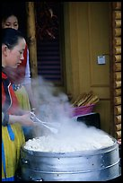 Naxi Women baking dumplings. Lijiang, Yunnan, China (color)