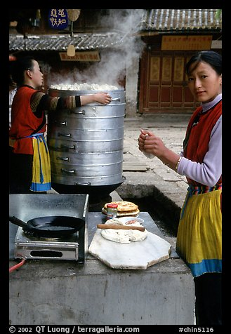 Naxi Woman preparing the baba flatbreat. Lijiang, Yunnan, China (color)