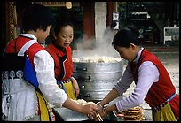 Naxi Women preparing the baba flatbreat. Lijiang, Yunnan, China (color)