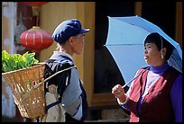 Two women conversing in the street. Lijiang, Yunnan, China