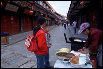 Schoolchildren get Naxi flatbread for breakfast. Lijiang, Yunnan, China