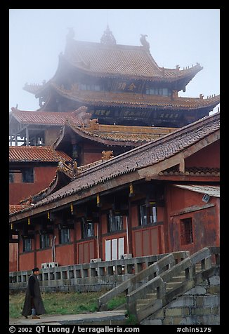 Monk beneath Jinding Si (Golden Summit) temple in the fog. Emei Shan, Sichuan, China (color)