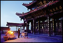 Pilgrim prays in the Jinding Si (Golden Summit) temple at dusk. Emei Shan, Sichuan, China ( color)