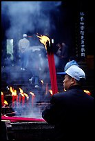 Pilgrim offering big incense stick. Emei Shan, Sichuan, China (color)