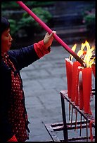 Woman Pilgrim lighting a large incense stick, Wannian Si. Emei Shan, Sichuan, China (color)