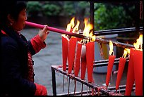 Woman Pilgrim lighting a large incense stick, Wannian Si. Emei Shan, Sichuan, China
