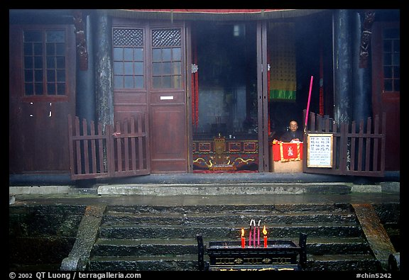 Monk looks to the courtyard inside Xixiangchi temple. Emei Shan, Sichuan, China