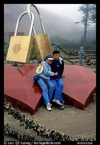 Lovers sit on top of two hearts surrounded by chain locks. Emei Shan, Sichuan, China