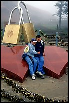 Lovers sit on top of two hearts surrounded by chain locks. Emei Shan, Sichuan, China ( color)