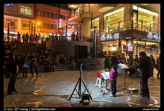 Tourists watch girl singing at night near the pier, Shueishe Village. Sun Moon Lake, Taiwan (color)