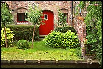 Small garden and brick house by the canal. Bruges, Belgium