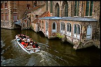 Tour boat goes by a church on a canal. Bruges, Belgium