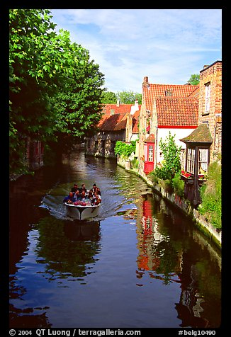 Boat on a canal lined with houses and trees. Bruges, Belgium (color)