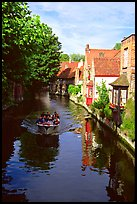 Boat on a canal lined with houses and trees. Bruges, Belgium