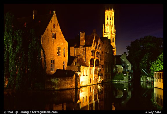 Old houses and beffroi reflected in canal at night. Bruges, Belgium (color)