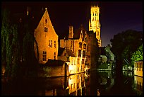 Old houses and beffroi reflected in canal at night. Bruges, Belgium