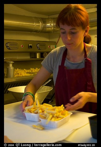 Woman serving fries in a booth. Bruges, Belgium
