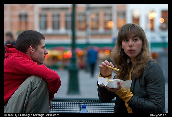 Young woman eating fries, Markt. Bruges, Belgium (color)
