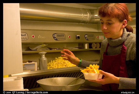 Woman preparing fries in a booth. Bruges, Belgium