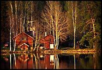 Wooden house reflected in a lake at sunset. Central Sweden