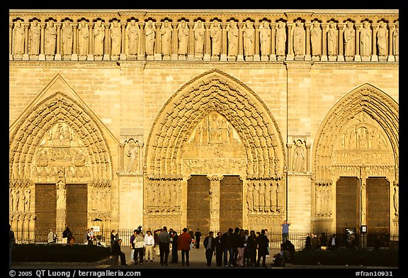 People standing in front of gates of Notre Dame Cathedral, late afternoon. Paris, France