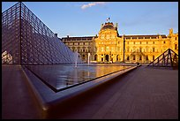 Pyramid, basins, and Sully Wing  in the Louvre, sunset. Paris, France