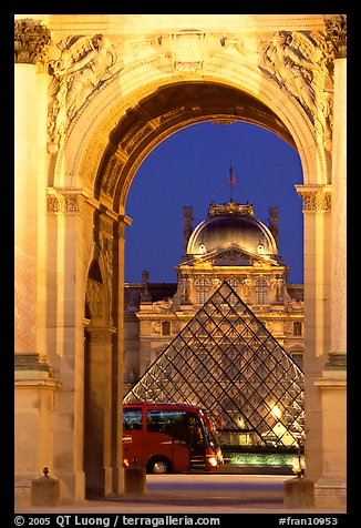Louvre, pyramid, and bus seen through the Carousel Arch at night. Paris, France (color)