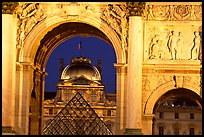 Louvre and  pyramid  seen through the Carousel triumphal arch at night. Paris, France