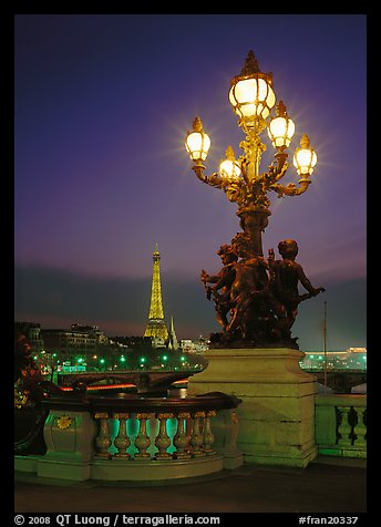Bronze lamp post with scultpure on Pont Alexandre III, and Eiffel Tower at night. Paris, France (color)