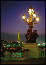 Bronze lamp post with scultpure on Pont Alexandre III, and Eiffel Tower at night. Paris, France
