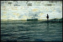 Man standing at water level fishing in the Seine River. Paris, France